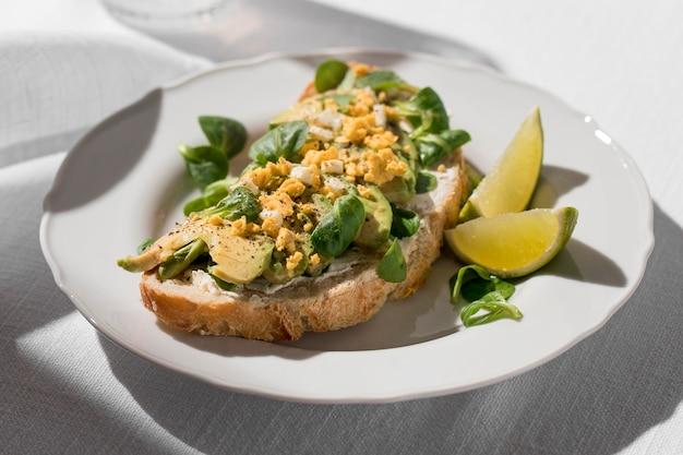 Alto angolo di pane tostato di avocado sulla piastra con lime
