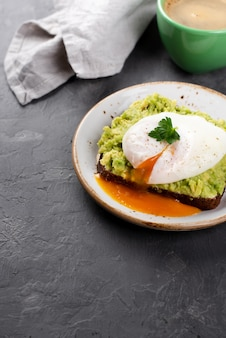 High angle of avocado toast with poached egg and cup of coffee