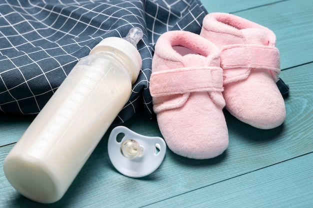 High angle of baby shoes and bottle with pacifier