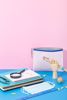 High angle of back to school supplies with notebook and magnifying glass