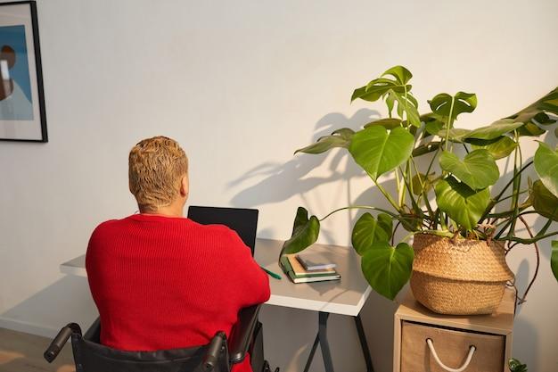 日光に照らされた机、コピースペースで自宅で仕事をしながら車椅子を使用している現代の混血の女性の高角度の背面図の肖像画
