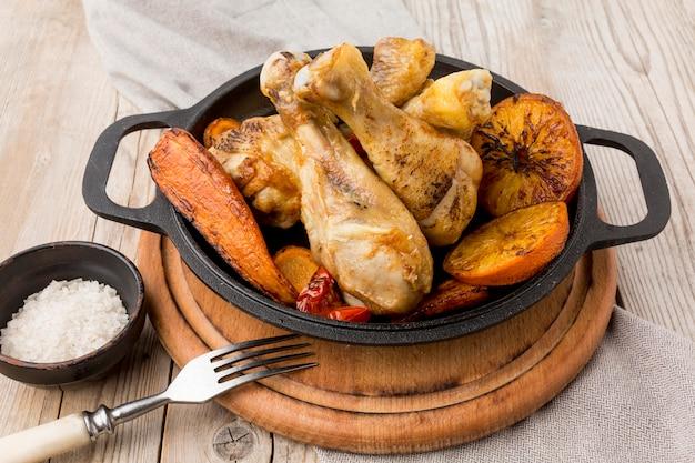 Запеченная курица и овощи под высоким углом на сковороде с вилкой
