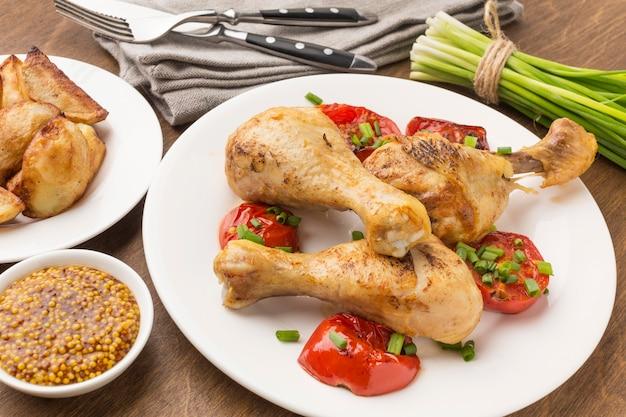 Pollo e pomodori al forno ad alto angolo sulla zolla con i cunei e la senape di digione