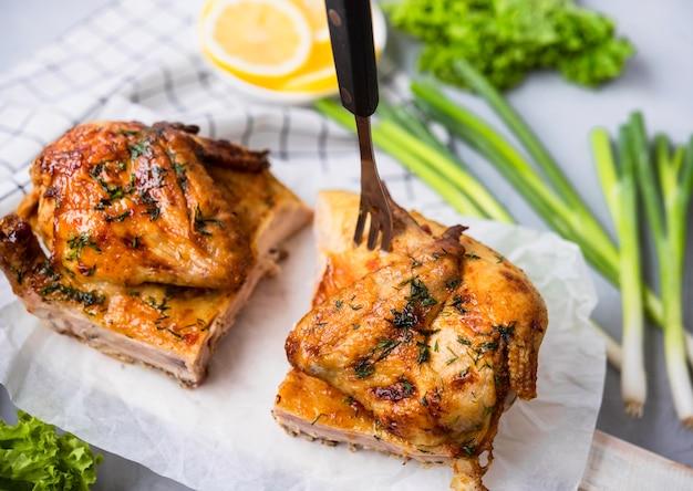 높은 각도로 구운 닭고기 반쪽을 샐러드와 함께