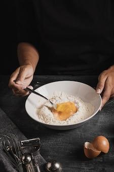 小麦粉と卵を混ぜたハイアングルのパン屋の手