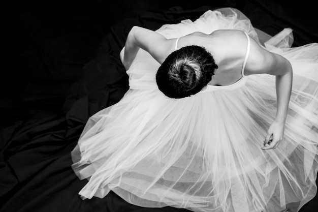High angle ballerina sitting grayscale