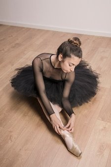 High angle ballerina tying pointe shoe