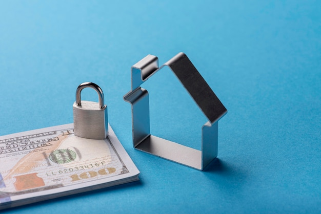 High angle of banknotes with lock and house