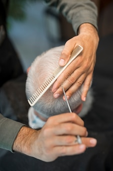 High angle of barber giving elder male client a haircut