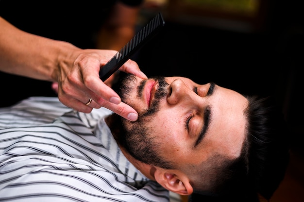 High angle barber looking at client's beard