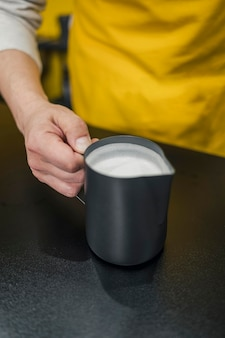 High angle of barista holding cup of milk