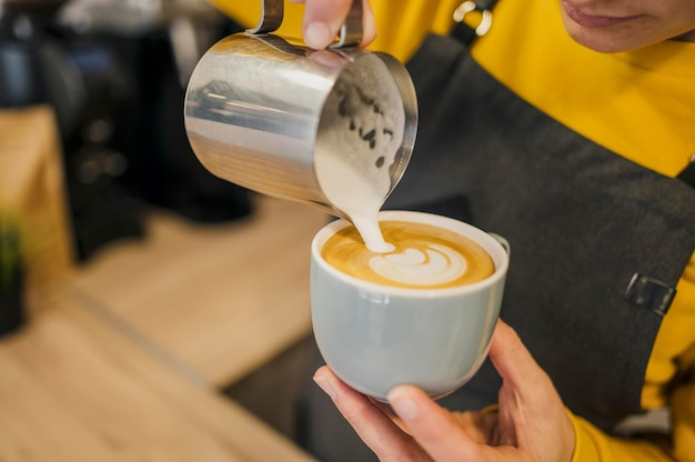 High angle of barista pouring milk in coffee