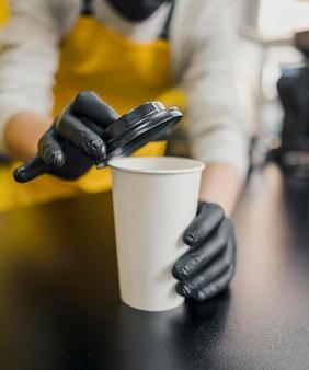 Alto angolo di barista con guanti in lattice che mettono il coperchio sulla tazza di caffè