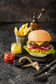 High angle beef burger on cutting board with fries and sauce