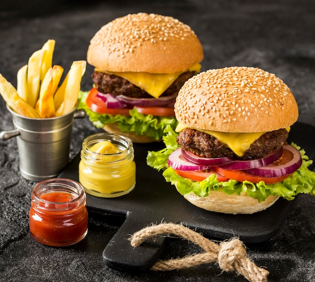 High angle beef burgers on cutting board with fries and sauce