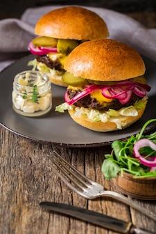 Hamburger di manzo ad alto angolo con sottaceti sul tagliere