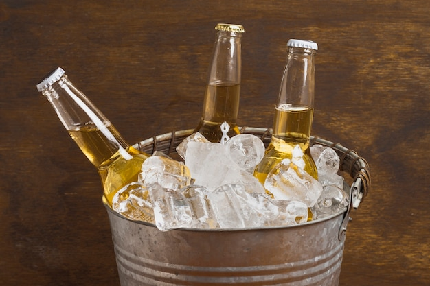 High angle beer bottles in ice cube bucket