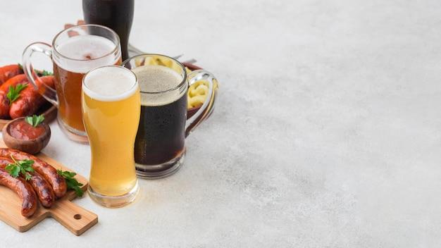 Бокалы для пива и сосиски под высоким углом