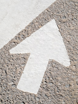 High angle of big white arrow on asphalt