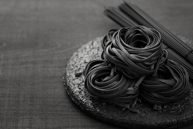 High angle of black tagliatelle on plate with spaghetti