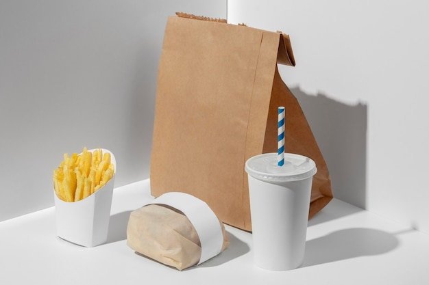 High angle blank fast food cup with packaged burger, fries and blank paper bag