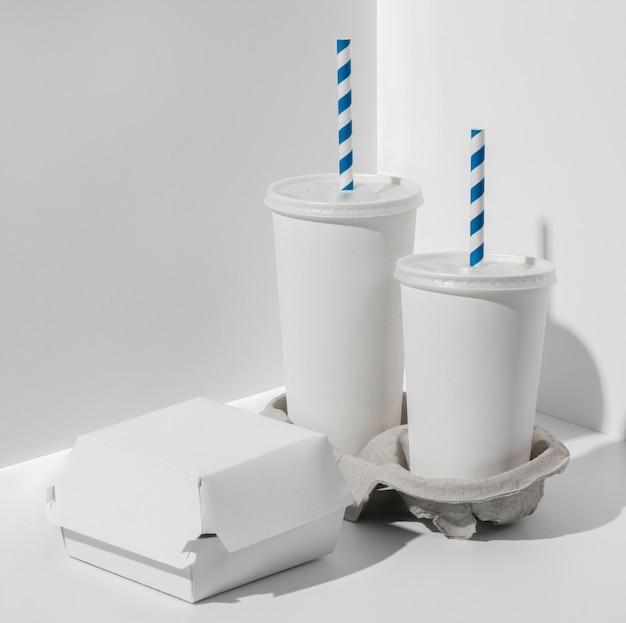 Tazze di fast food in bianco ad alto angolo con confezione di hamburger
