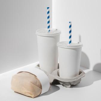 Tazze di fast food in bianco ad alto angolo con hamburger confezionato