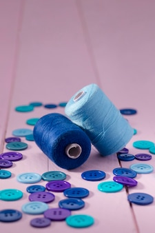 High angle of blue buttons and thread reels
