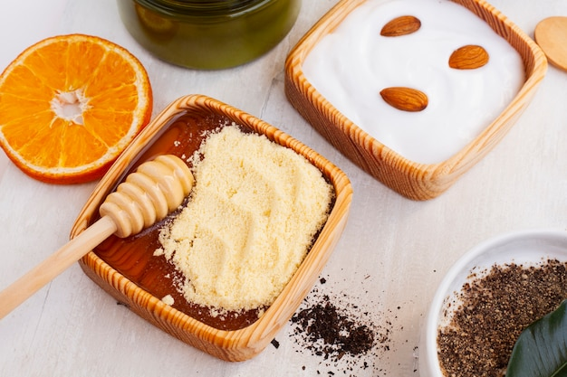 High angle of body butter and orange on wooden table