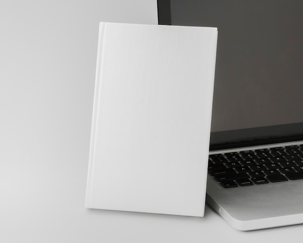 High angle book beside laptop