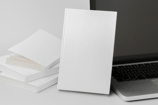 High angle books beside laptop on desk