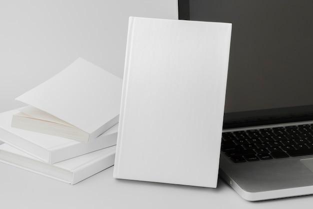 机の上のノートパソコンの横にある高角度の本