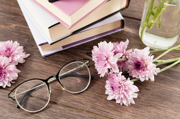 High angle of books flowers and glasses on wooden table