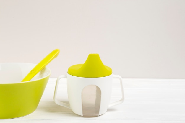High angle of bowl and baby bottle with copy space