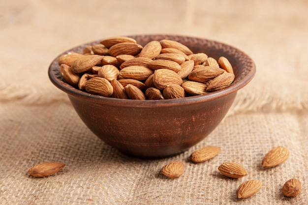 High angle of bowl on burlap with almonds