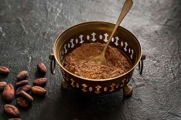 High angle of bowl with cocoa powder and cocoa beans