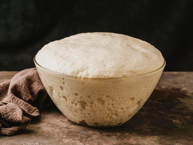 Angolo alto della ciotola con pasta crescente per pizza