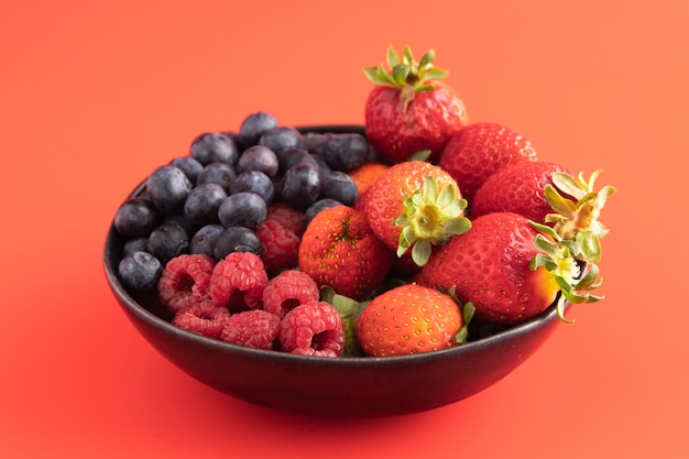 High angle of bowl with strawberries, blueberries and raspberries
