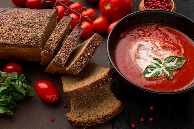 High angle of bowl with winter tomato soup and toast