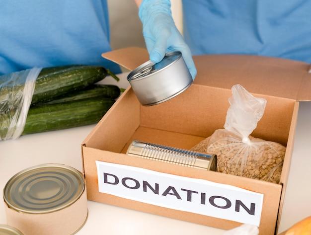 Alto angolo di scatola con donazione di cibo in preparazione