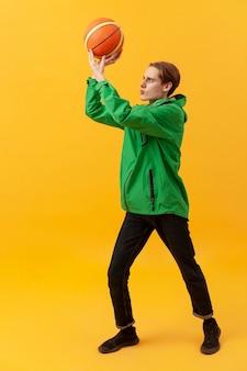 Высокий угол мальчик играет с баскетбольным мячом