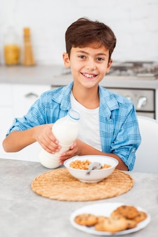 High angle boy pouring milk on cereals