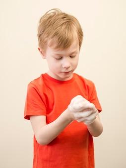 Mani di lavaggio del ragazzo dell'angolo alto Foto Gratuite