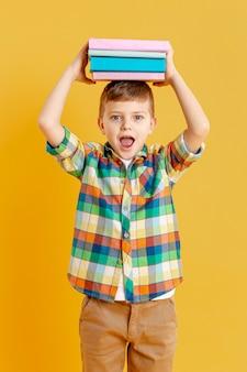 彼の頭の上の本を持つ高角少年