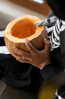 High angle of boy with pumpkin costume concept Premium Photo