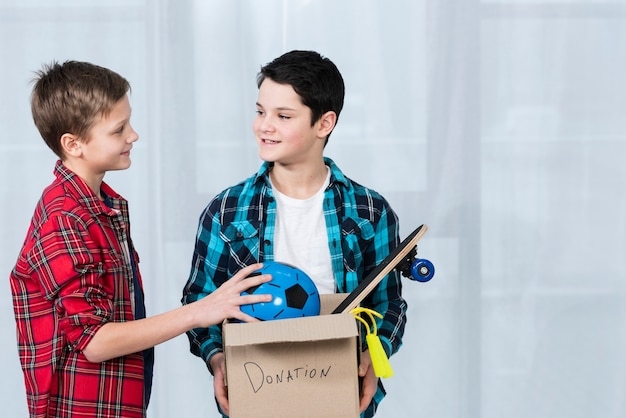 High angle boys holding donation box