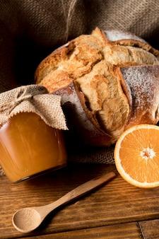 Alto angolo di pane con barattolo di marmellata di arance