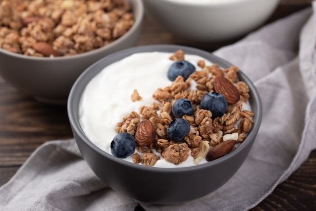 High angle of breakfast cereal in bowl with blueberries and yogurt