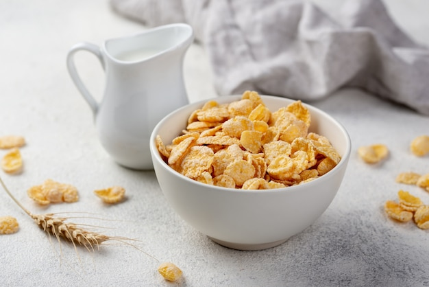 High angle of breakfast corn flakes in bowl with milk and wheat