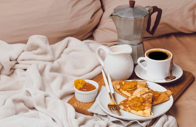 Alto angolo di crepes per la colazione con marmellata e caffè